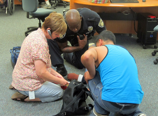 (From left) Karen McCoy, Campus Officer Kenneth Coleman and Christian Jimenez circle an unknown student who collapsed in Grossmont's library (Photo: Russ Lindquist))