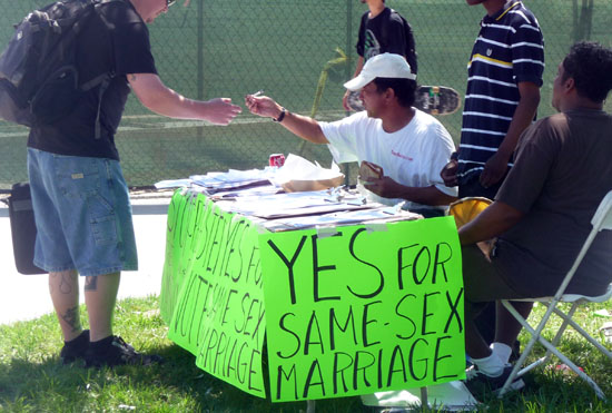 Jacobi Malone sits at petition booth for same sex marriage.